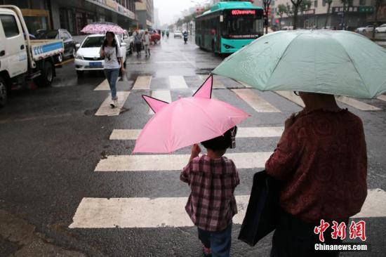 7月17日,陕西关中区域迎来降雨气候,估计降雨持续3日。据陕西省气象台音讯,西安自六月中下旬以来至今,是同时期36年来最凉爽的一个时段。图为西安民众雨中出行。中新社记者 张远 摄