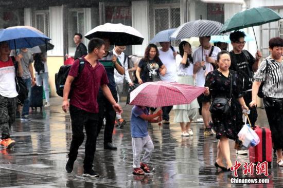 7月17日,陕西关中地区迎来降雨天气,预计降雨持续3日。据陕西省气象台消息,西安自六月中下旬以来至今,是同时期36年来最凉快的一个时段。图为西安民众雨中出行。中新社记者 张远 摄