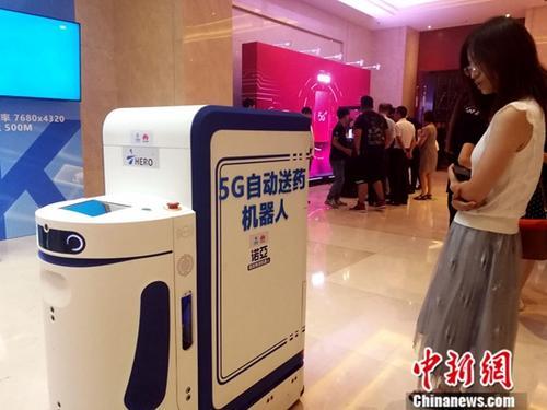 """7月18日,5G自动送药机器人吸引观众围观。当日,中国移动天津公司在天津举办""""双千兆城市发布会暨战略合作伙伴签约仪式"""",现场展示了""""千兆5G移动网络+千兆光纤宽带网络""""的网络服务能力,标志着天津市通信网络迈入""""双千兆""""时代。<a target='_blank' href='http://www.chinanews.com/'>中新社</a>记者 张道正 摄"""