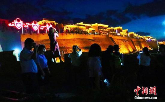 """7月18日晚,新疆喀什古城景区新打造的""""古城印象""""餐饮及文化一条街吸引了不少游客在此留影""""打卡""""。王小军"""