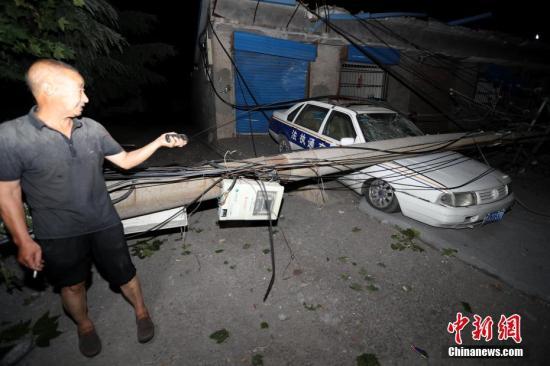 图为7月20日凌晨,村民在观看受爆炸影响损毁的车辆。 中新社记者 王中举 摄