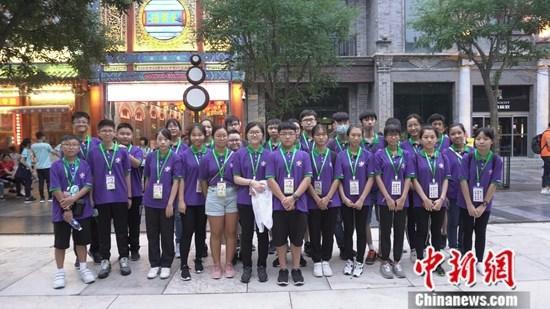 """7月20日,香港童军总会的成员在北京前门参访。当天傍晚,参加""""同心同根万里行2019""""的香港14家青少年制服团体成员等300余人抵达北京,开启为期9天的北京、山东参访交流活动。中新社</a>记者 陈佩龄 摄"""
