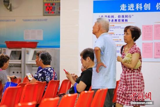 民众在股市营业厅用手机看科创板走势。 殷立勤 摄
