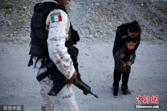 这名国民警卫队告诉移民Lety Perez,他不能让她通过,他只是在做自己的工作,而Lety Perez一再恳求。这种情况持续了几分钟,突然Lety Perez拉着儿子跑了,进入干涸的河堤,走到中间,在那里这名守卫已经没有管辖权了。图片来源:视觉中国