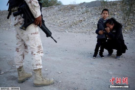 资料图:7月26日消息,路透社摄影师拍摄的照片使人们关注到墨西哥的移民危机以及墨西哥国民警卫队在遏制中美洲移民方面所发挥的作用。当地时间2019年7月22日,墨西哥华雷斯,一名危地马拉移民带着她的孩子在离美国边境只有几英尺远的地方,被一名墨西哥国民警卫队士兵拦住了,她捂着脸哭泣。