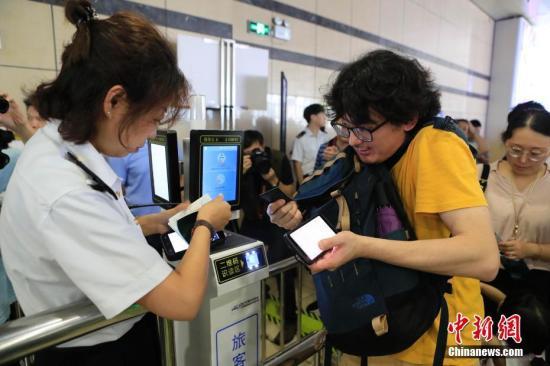 资料图:旅客使用护照及二维码车票确认信息后上车。殷立勤 摄