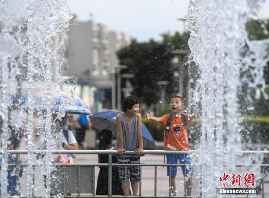 材料图:女童正在喷泉边躲寒乘凉。a target='_blank' href='http://www.chinanews.com/'中新社/a记者 张怯 摄