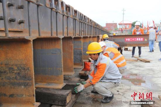 """7月30日下午,中国""""东极""""地区最难下穿工程——牡佳客专米厂路下穿框构主体顺利贯通,中国高铁施工单位又攻克一重大高寒高速铁路施工难题。全长375公里的牡佳高铁是中国《中长期铁路网规划》的主要建设项目之一和国家""""十三五""""规划的铁路工程项目,是东北高速铁路环线的重要组成部分。中新社发 徐明禹 摄"""
