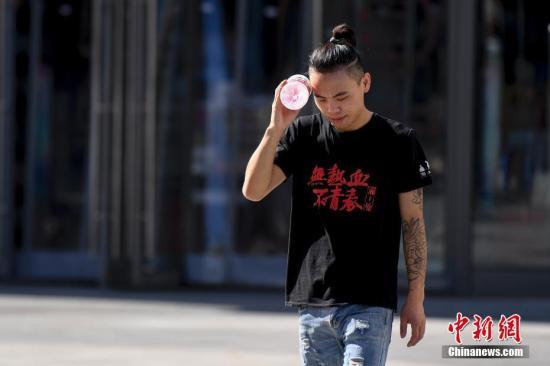 一位市民用水瓶遮挡太阳。杨华峰 摄