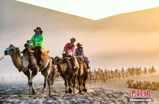 游客骑骆驼畅游鸣沙山,体验丝路风情。王斌银 摄