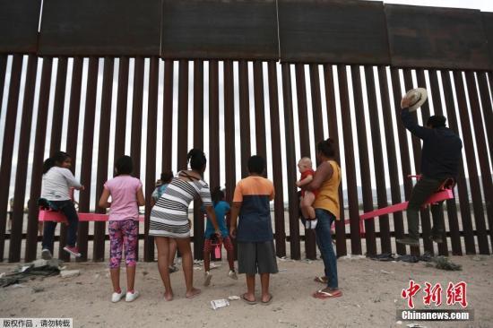 8月1日消息,近日,美国加州两位教授利用美墨边境高墙的空隙,设置了横跨两国的跷跷板,跷跷板一边在美国,一边则在墨西哥,让美墨两边的大人小孩隔着高墙仍能一同玩耍。