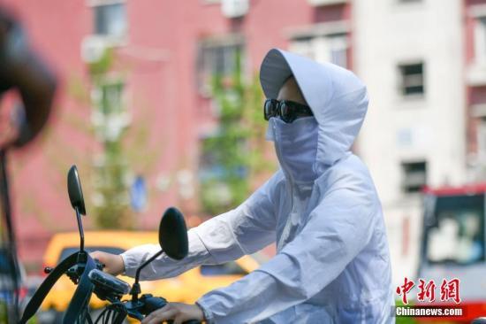 8月1日,北京高温天气持续,出行的市民用各种装备来遮挡炙热的阳光。中新社记者 张兴龙 摄