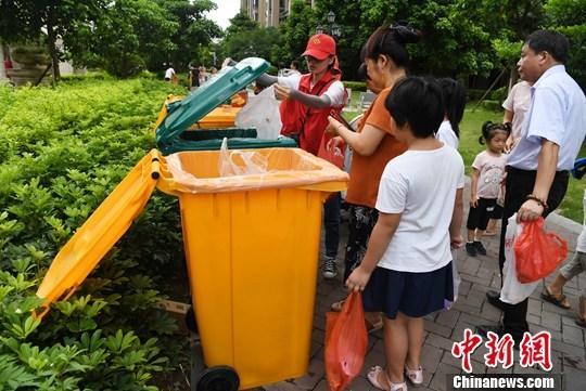 8月1日,福州仓山区盖山镇一社区居民在志愿者引导下分类投放垃圾。当日,福州市生活垃圾分类执法行动启动。中新社记者 张斌 摄