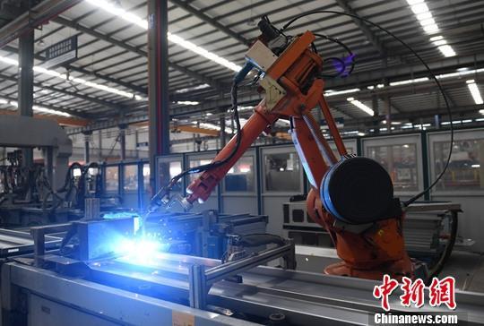 资料图:工厂车间内一台机械臂在焊接产品。中新社记者 王刚 摄