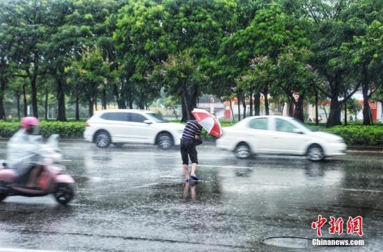 资料图:民众在雨中出行。翟李强 摄