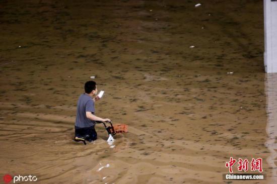 8月1日,河南鄭州突降暴雨,市民在齊腰深的水中艱難前行。圖片來源:ICphoto