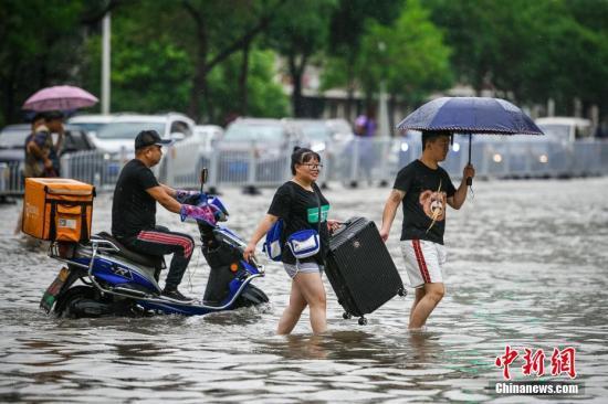 民众涉水出行。中新社记者 佟郁 摄
