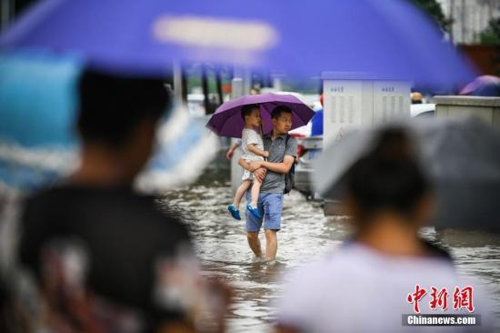 材料图:公众正在雨中出止。a target='_blank' href='http://www.chinanews.com/'种孤社/a记者 佟郁 摄