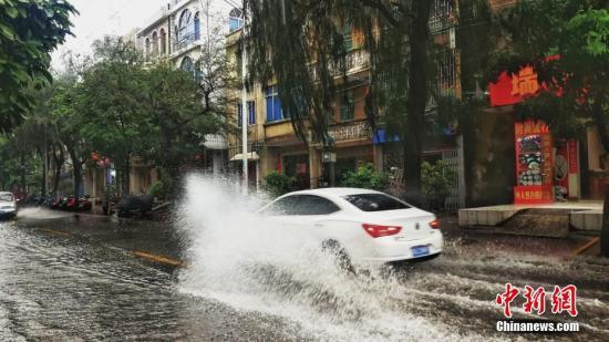 """8月2日晚19时许,广西北海市狂风暴雨。台风""""韦帕""""给广西沿海带来大量雨水。当天,北海市区多个路段出现了严重积水,有民众受伤,海水潮位高涨。""""韦帕""""于1日晚22时左右进入北部湾海域后,一直在北海市近海海域缓慢西移,沿着海岸线走了十多个小时,于2月下午16时许才移动到广西钦州近海。""""韦帕""""在北海近海逗留期间,北海降雨不断,且不时刮起大风。图为民众积水中出行。 翟李强 摄"""