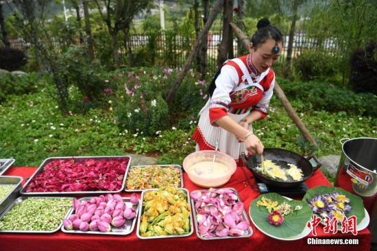 """资料图:云南丽江千古情景区举行""""百花宴"""",邀请各地游客品尝利用鲜花制作的美食,体验云南独特的美食风俗。杨晨 摄"""