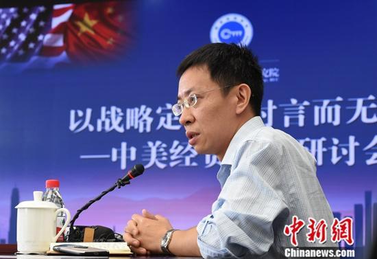 """8月5日,""""以战略定力应对言而无信——中美经贸问题研讨会""""在北京中国人民大学举行。多位专家学者就此主题进行发言讨论。本次研讨会由中国人民大学国家发展与战略研究院主办。图为北京大学国家发展研究院党委书记、教授余淼杰发言。中新社记者 侯宇 摄"""