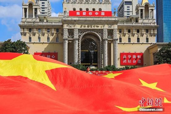 8月6日,在上海展览中心,民众挥舞着手中的国旗与党旗,共同唱响《我爱你中国》,为祖国70周年华诞献礼。殷立勤 摄