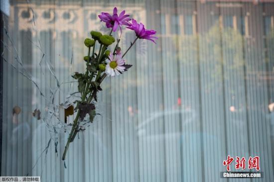 资料图:当地时间2019年8月5日,美国俄亥俄州代顿,众多民众自发来到发生大规模枪击事件的酒吧前,摆放鲜花悼念遇难者,有的民众将鲜花插在被子弹打穿的玻璃上。
