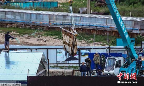 资料图:当地时间6月20日,俄罗斯,海参崴,工人们在斯雷德尼亚湾用起重机把鲸鱼移走。