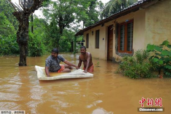当地时间8月9日,印度喀拉拉邦科奇国际机场,大量客机停放在停机坪上,机场部分设施被洪水淹没。喀拉拉邦科奇国际机场国际机场已于当日关闭。近日,印度南部喀拉拉邦连续遭遇暴雨,导致超过20人死亡。图为印度南部喀拉拉邦的民众在洪水中涉水前行。