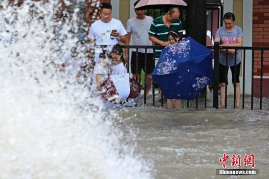 """8月10日,上海北华路出现严重积水,市民路边看""""海""""。上海中心气象台于当日14时20分更新暴雨黄色预警信号为暴雨橙色预警信号。受台风""""利奇马""""影响,新闻健德堂,预计未来6小时内中心城区、嘉定、闵行、奉贤、浦东等地最大小时雨强可达60-80毫米。中新社记者 殷立勤 摄"""