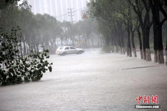 8月10日,浙江温岭,一辆轿车在积水严重的道路上行驶。中新社发 金云国 摄