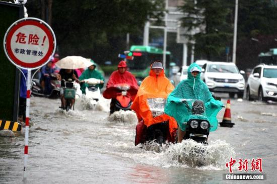 民众冒雨涉水出行。(资料图)/p中新社记者 王中举 摄