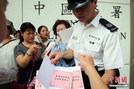 图为市民将慰问卡及签发递交中区警署值日警官。/p中新社记者 洪少葵 摄