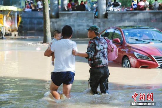 """超强台风""""利奇马""""来袭,浙江各方力量开展救援行动。图为一名救援人员指引被困市民进行转移。中新社记者 李祥 摄"""