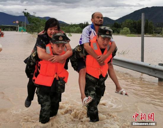 """8月10日,两名武警背着受困者涉水转移。当日,受今年第9号台风""""利奇马""""影响,浙江台州临海多处被淹,民众受困,各方力量紧急出动转移受困民众。台州武警供图"""