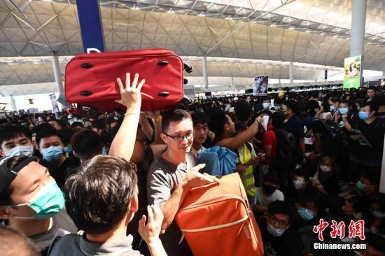 8月12日下午三时许,大批非法集结于香港国际机场的示威者拆走铁马,进入原先只限持机票旅客才可进入的离境大堂禁区前通道位置。受非法集结影响,大批登机旅客受阻,航班取消。<a target='_blank' href='http://www.sjizh.com/'>中新社</a>记者 麥尚旻 摄