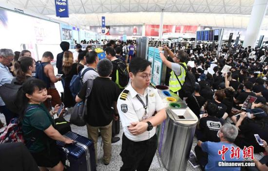 8月12日下午三时许,大批非法集结于香港国际机场的示威者拆走铁马,进入原先只限持机票旅客才可进入的离境大堂禁区前通道位置。受非法集结影响,大批登机旅客受阻,航班取消。 <a target='_blank' href='http://bpmf.net/'>中新社</a>发