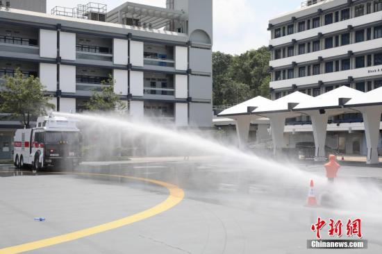 """8月12日,香港警方在位于粉岭的警察机动部队总部,首次展示人群管理特别用途车,即俗称的""""水炮车""""。车上设有一个水箱和催泪溶液储存装置,车顶则配置2支喷水装置,可根据需要而选用喷射水柱模式,以及喷洒催泪水剂等驱散人群。图为警方示范水炮车的喷水装置。 <a target='_blank' href='http://www.chinanews.com/'>中新社</a>记者 谢光磊 摄"""