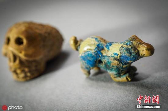 当地时间2019年8月12日,意大利庞贝古城,考古学家在庞贝发现了一个树干,里面有各种各样有趣的东西,包括石头、骨头等被认为在仪式中使用的物体。这些东西中有许多都被认为是一个巫师的收藏品。图片来源:icphoto