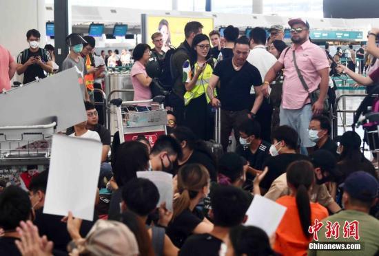 8月13日下午,大批示威者以机场手推车等堵塞香港国际机场1号客运大楼旅客登机行段及保安闸门。中新社记者 麦尚旻 摄