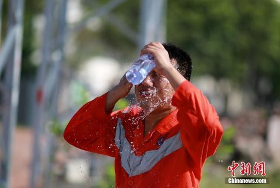 资料图为高温作业中工人洗脸消暑。 苏志刚 摄