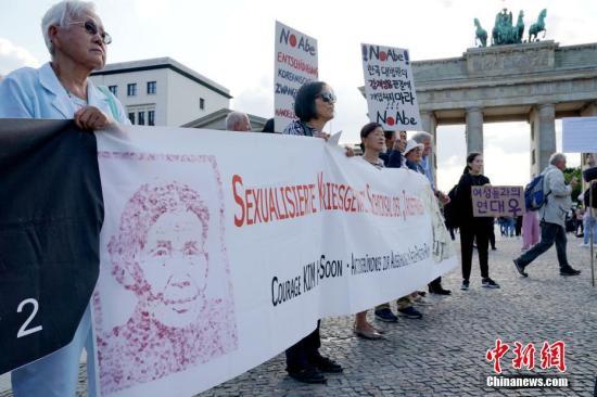 """8月14日,在德的韩国和日本民间团体于第七个世界""""慰安妇""""纪念日之际在柏林勃兰登堡门前举行集会,再次敦促日本政府正式向""""慰安妇""""制度暴行受害者道歉,并作出赔偿。中新社记者 彭大伟 摄"""