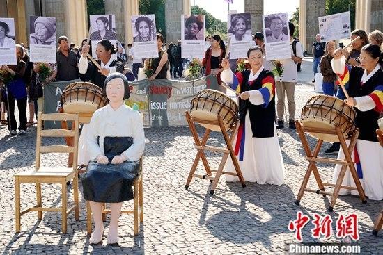 """8月14日,在德的韩国和日本民间团体于第七个世界""""慰安妇""""纪念日之际在柏林勃兰登堡门前举行集会,再次敦促日本政府正式向""""慰安妇""""制度暴行受害者道歉,并作出赔偿。一座""""和平少女像""""亦出现在当天的活动现场。记者 彭大伟 摄"""