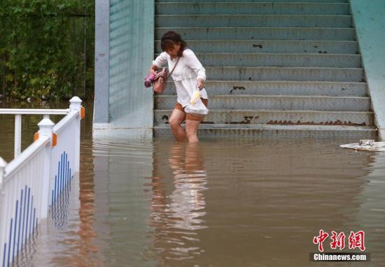市民在积水中行走。中新社发 钟欣 摄