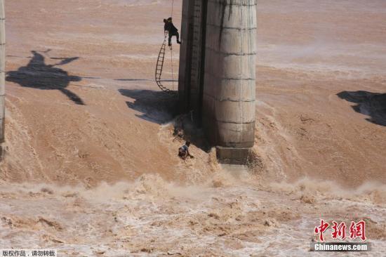当地时间8月19日,印度查谟,四名渔民被困水位上涨的在建拦河坝上,印度空军派出直升机进行救援。
