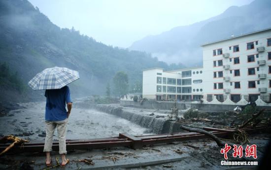 资料图:2019年8月下旬,四川阿坝州多地因强降雨发生暴雨灾害。图为三江镇一游客站在被洪水冲毁护栏的大桥上。中新社记者 刘忠俊 摄