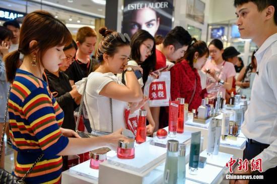 资料图:2019年,海南新增两家离岛免税购物店,女顾客们在化妆品柜台前购买商品。 中新社记者 骆云飞 摄