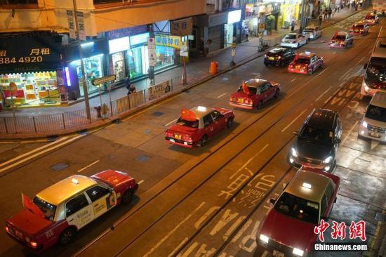 """资料图:""""守护香港大联盟""""联同香港的士司机从业员总会发起""""守护香港·风雨同舟""""大行动,多辆出租车车身贴着海报,车尾悬挂五星红旗依次有序驶向主干道,呼吁社会反对暴力。<a target='_blank' href='http://www.chinanews.com/'>中新社</a>记者 张炜 摄"""