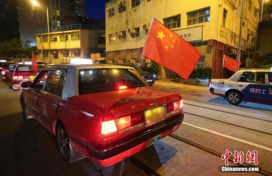 """资料图:8月23日晚,""""守护香港大联盟""""联同香港的士司机从业员总会发起""""守护香港·风雨同舟""""大行动,在港岛筲箕湾中心,有超过140多辆出租车车身贴着海报,车尾悬挂五星红旗依次有序驶向主干道,呼吁社会反对暴力。<a target='_blank' href='http://www.chinanews.com/'>中新社</a>记者 张炜 摄"""