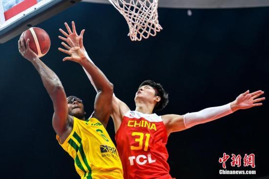 资料图:中国男篮球员在比赛中封盖对手上篮。 中新社记者 陈骥�F 摄
